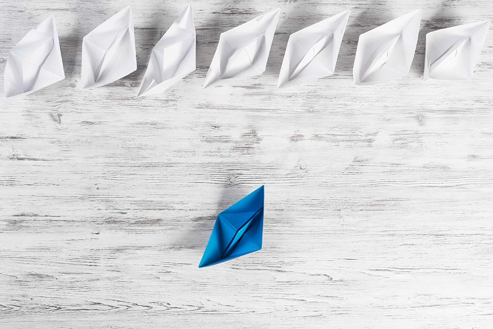 Set of origami boats on wooden table. Image used to illustrate agile leadership.